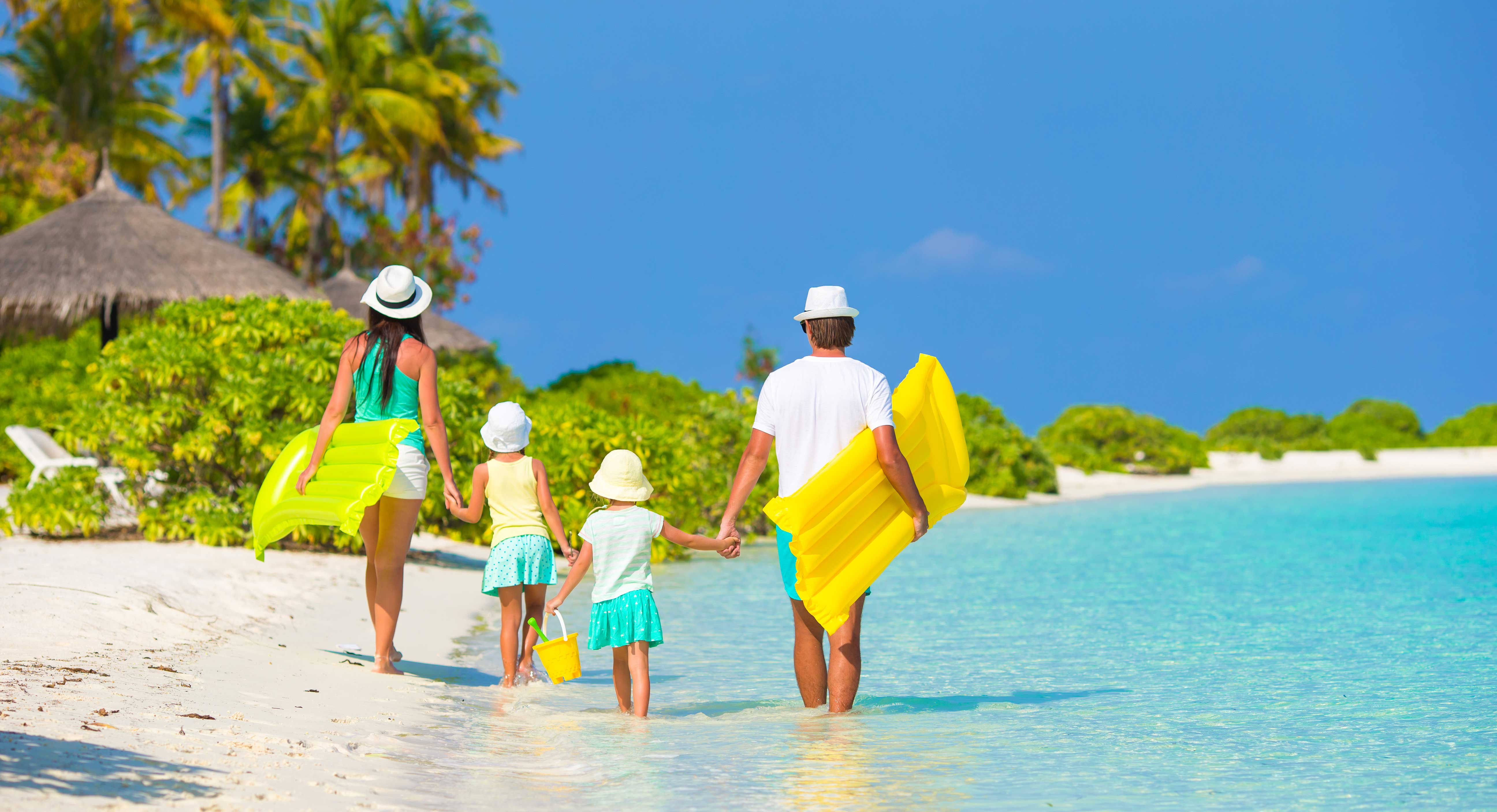 Family of four walking along the beach holding lilo sunbeds