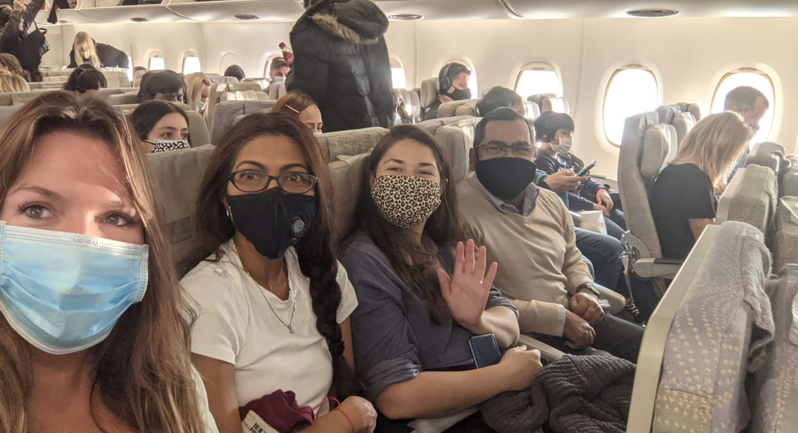 People sat on a plane wearing masks