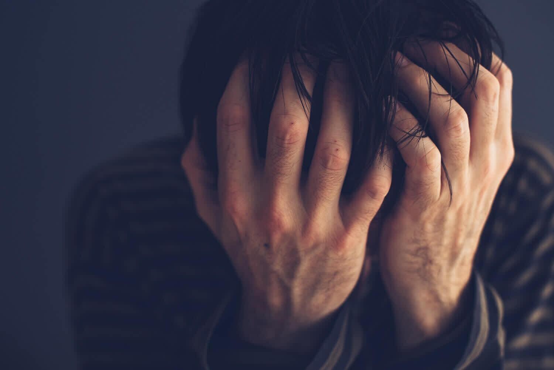 Opioid User Face in Hands.