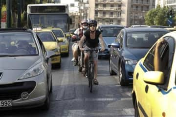 Elena Koniaraki rides her bicycle between cars at a central street in Athens