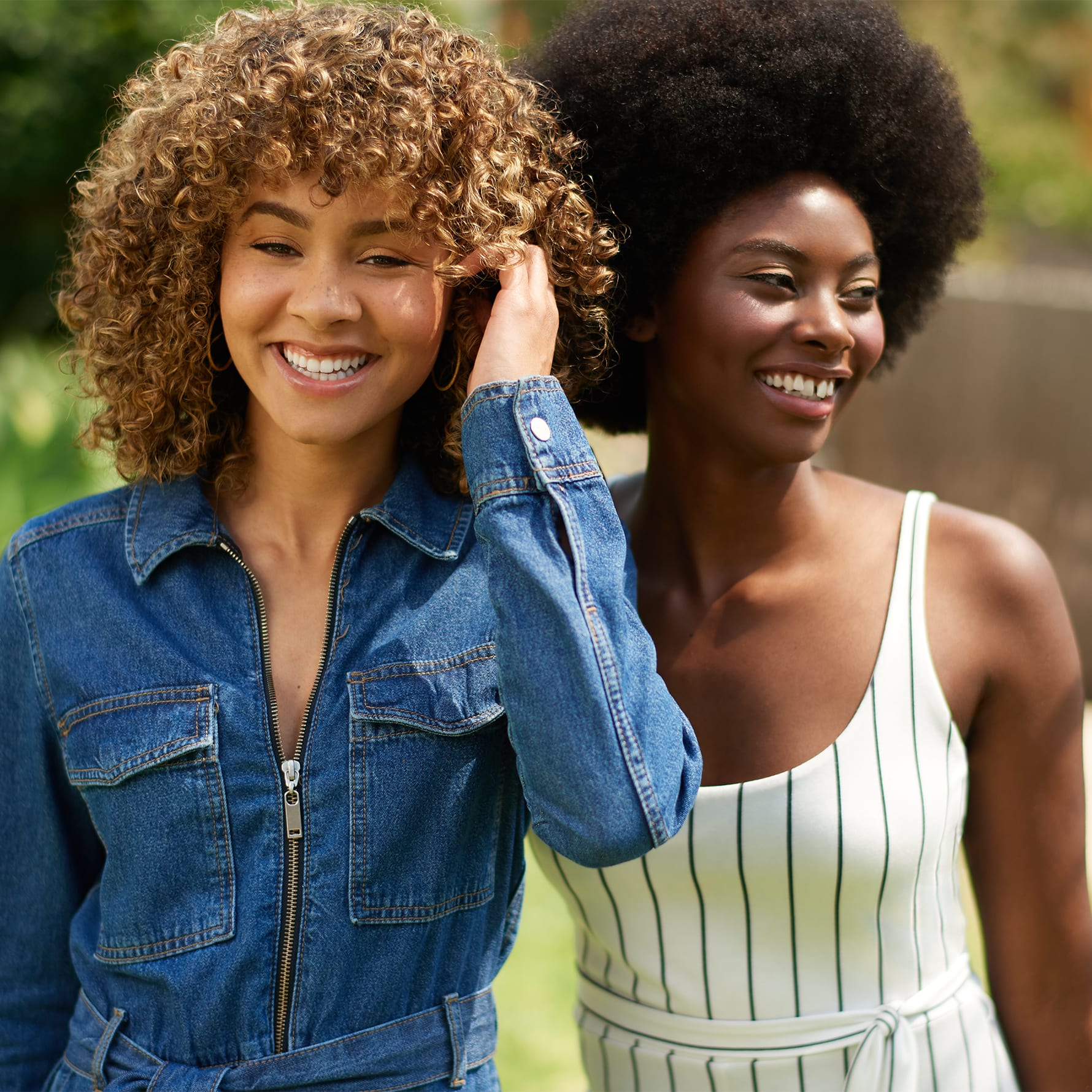 two curly hair women smiling