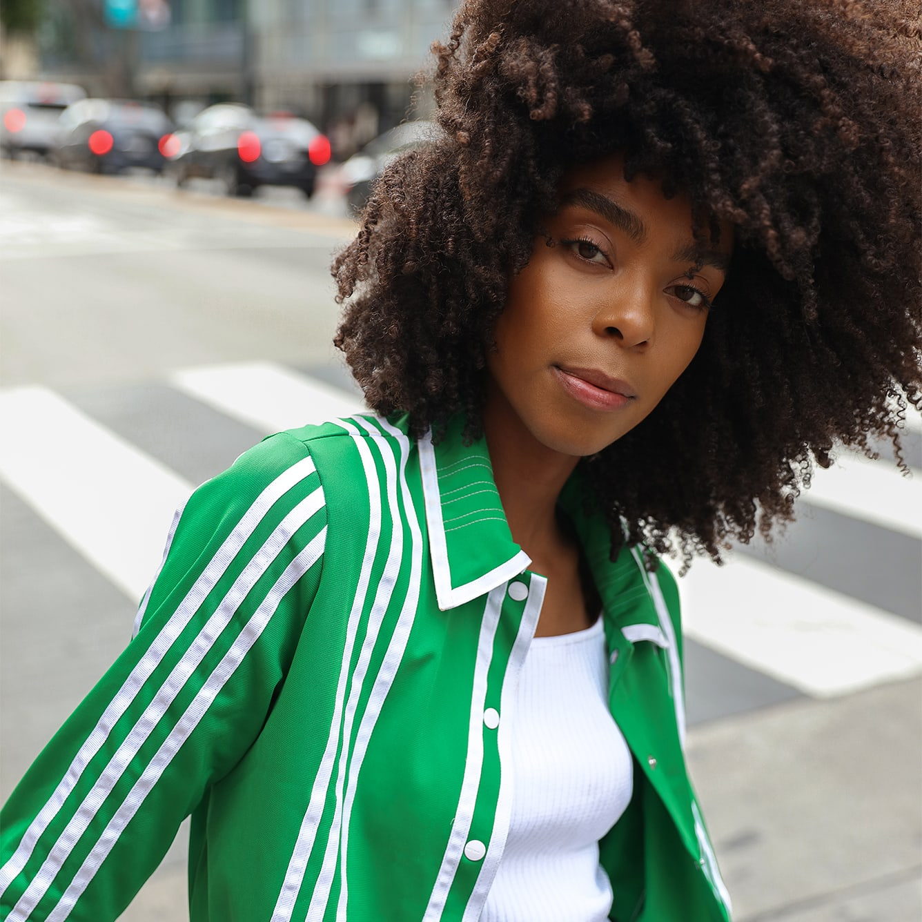 woman outside with super curly hair in a green track jacket