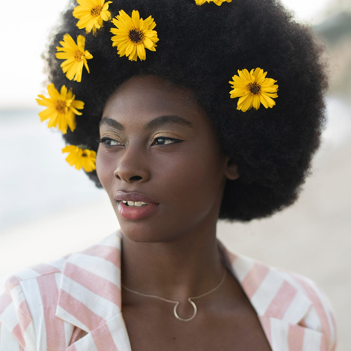 woman with a super curly fro and sunflowers in her hair