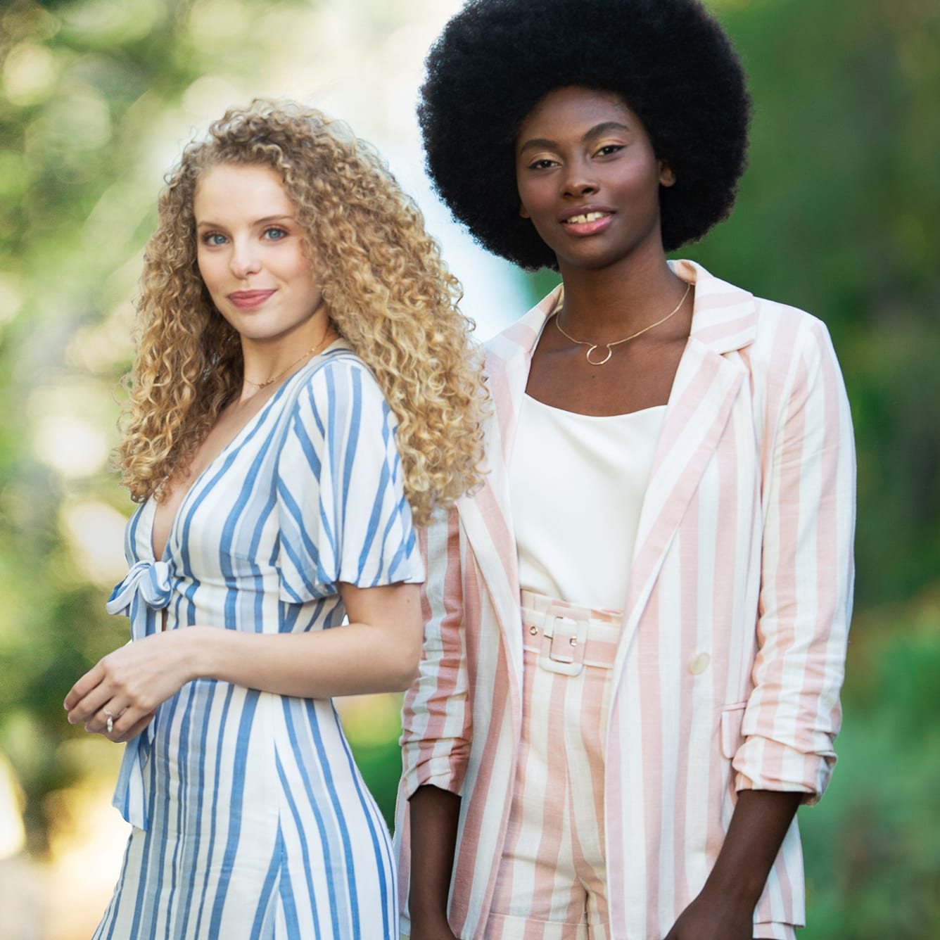 woman with long blonde curly hair and woman with a full curly afro