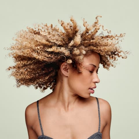 woman shaking her blonde curly hair