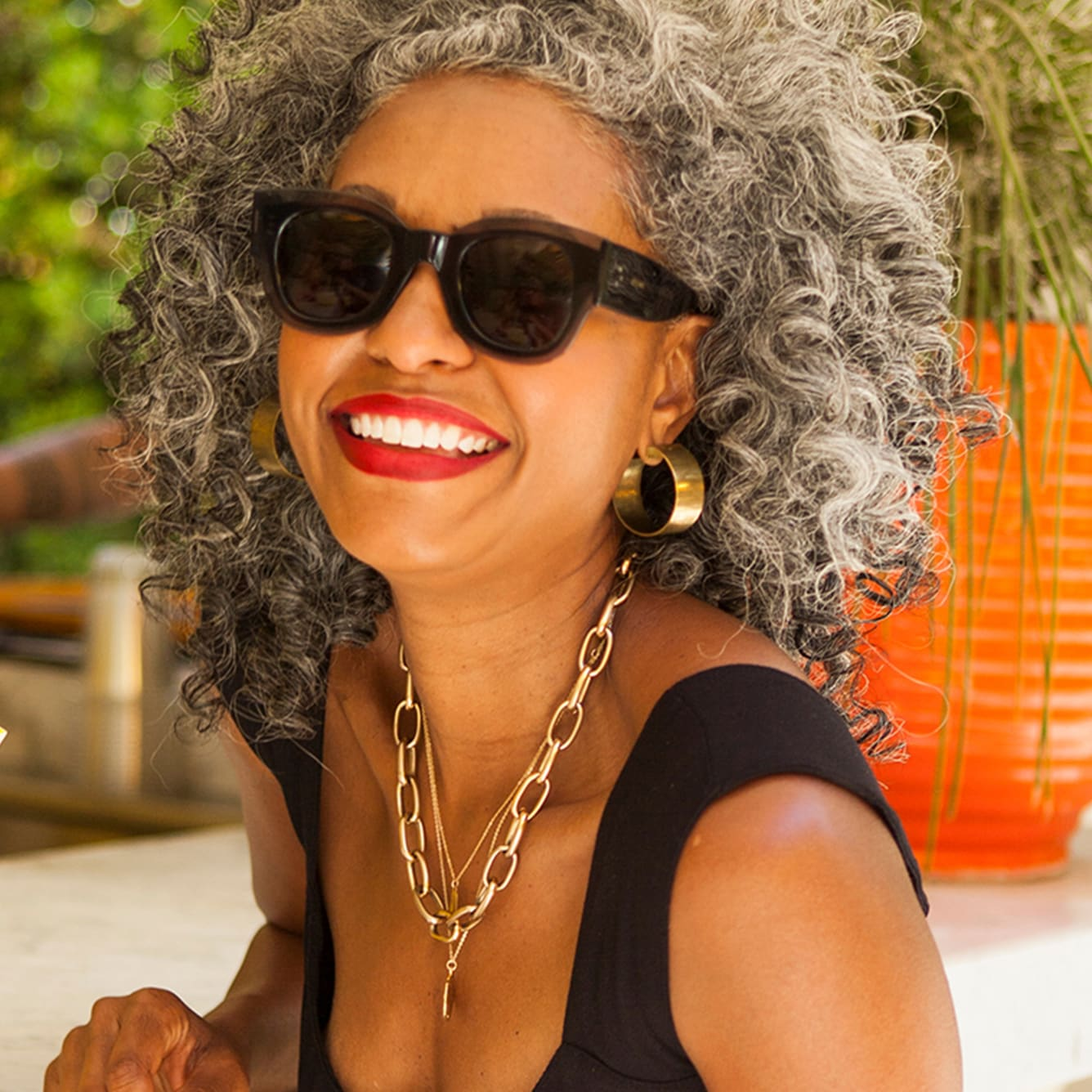 woman with silver curly hair smiling and wearing sunglasses