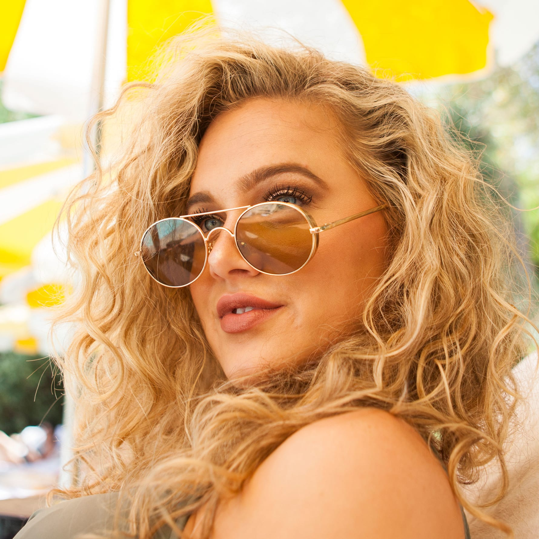 woman with blonde wavy hair wearing sunglasses