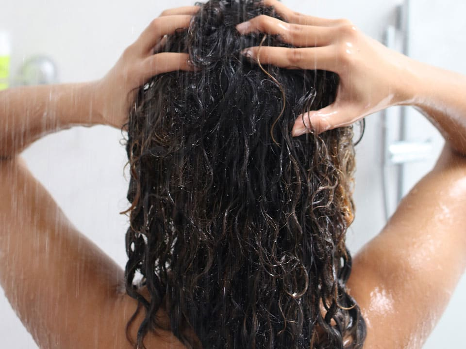 woman in the shower scrubbing wet dark curly hair