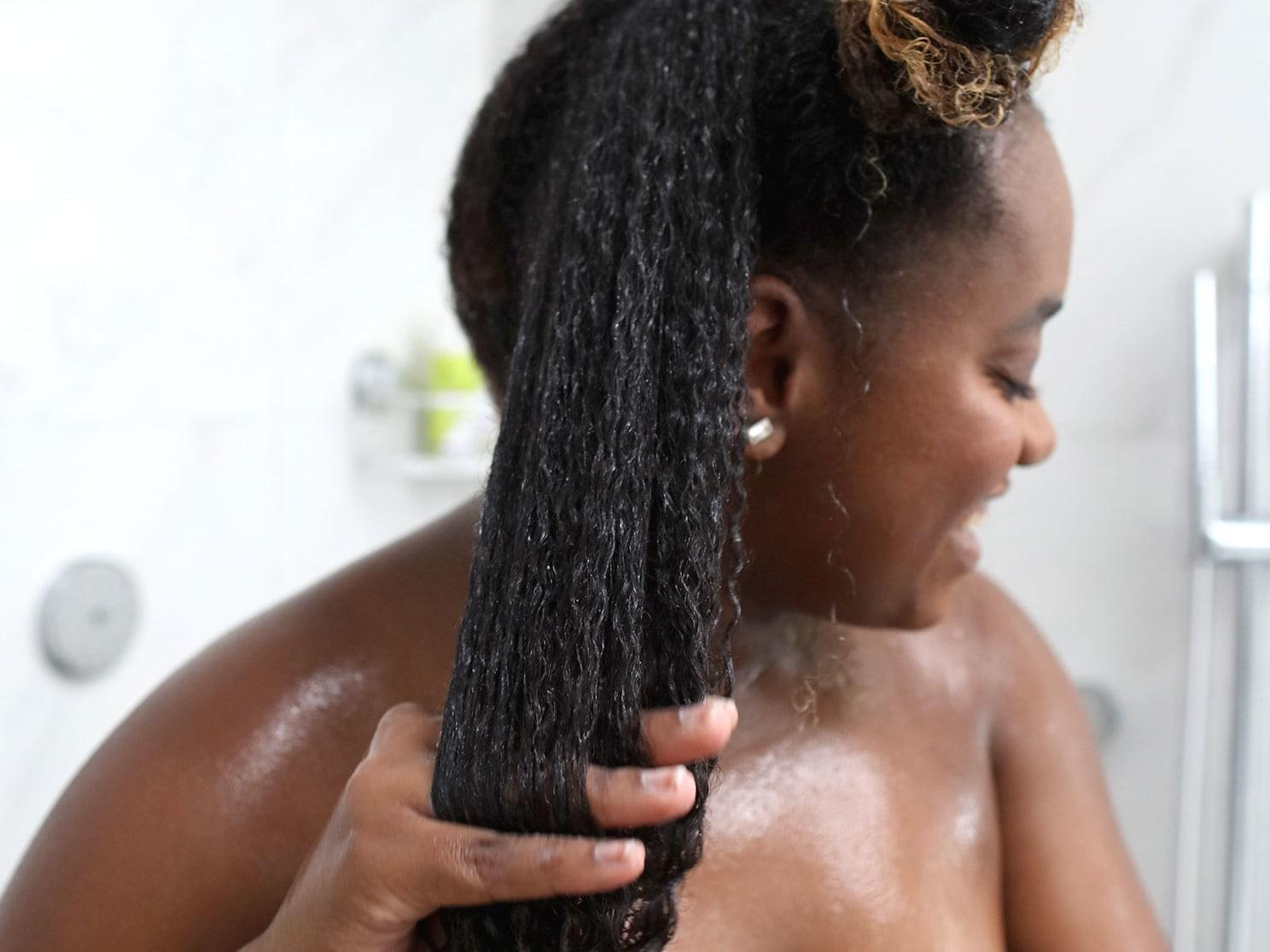 woman in the shower scrubbing wet dark curly hair