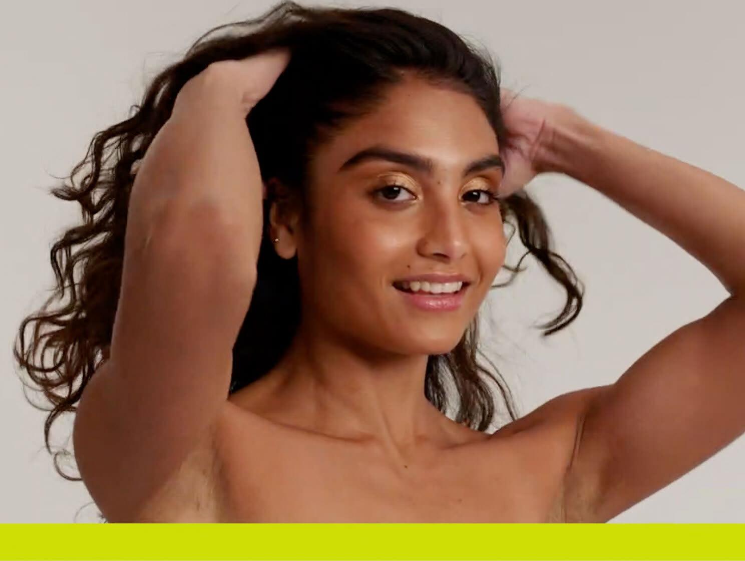 woman in shower washing dark curly hair