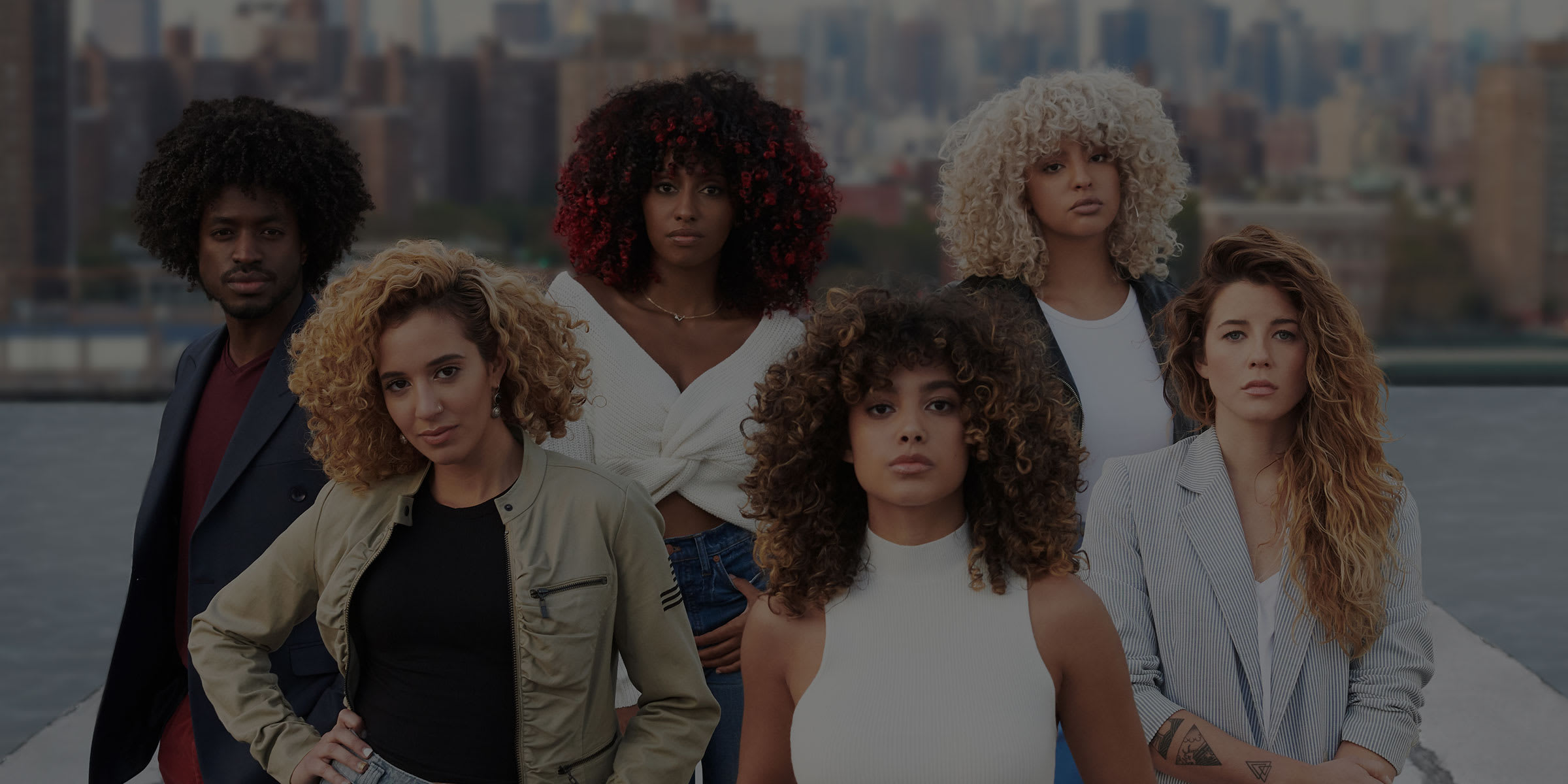 group of curly hair people in front of skyline