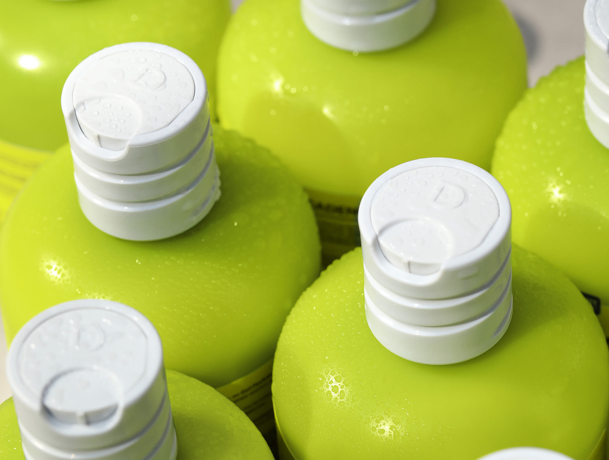 close up of green DevaCurl bottles and caps