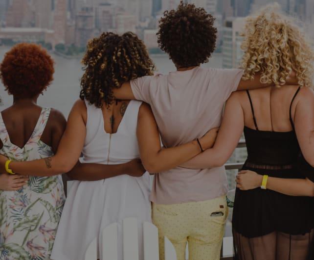 Grupowe ujęcie osób z lokami na tle panoramy miasta