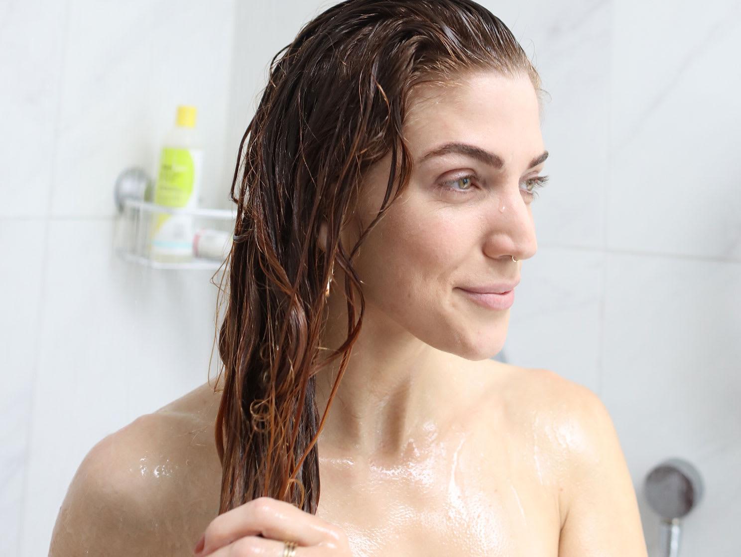 femme aux cheveux ondulés sous la douche