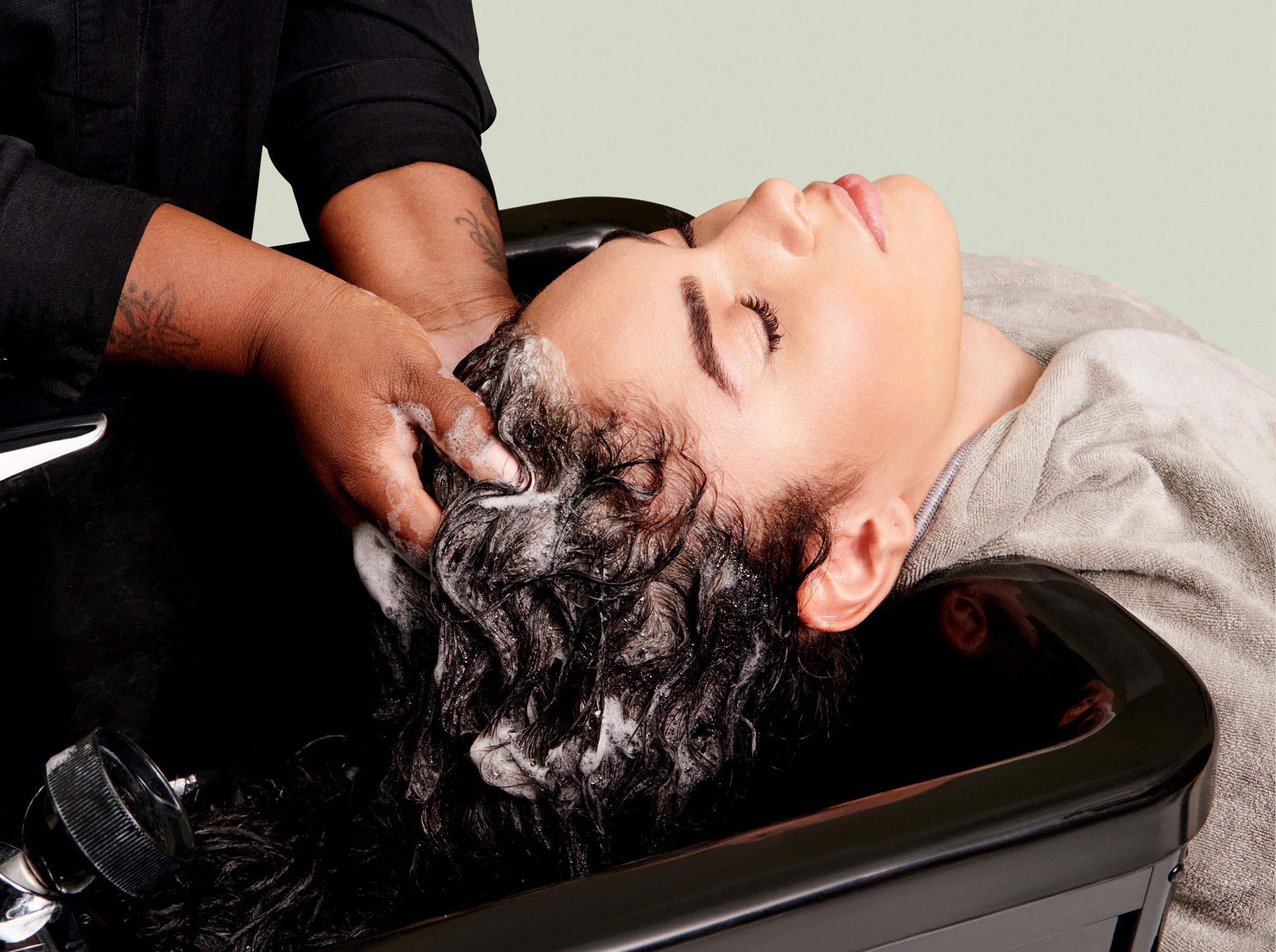 client at salon sink, hands in hair