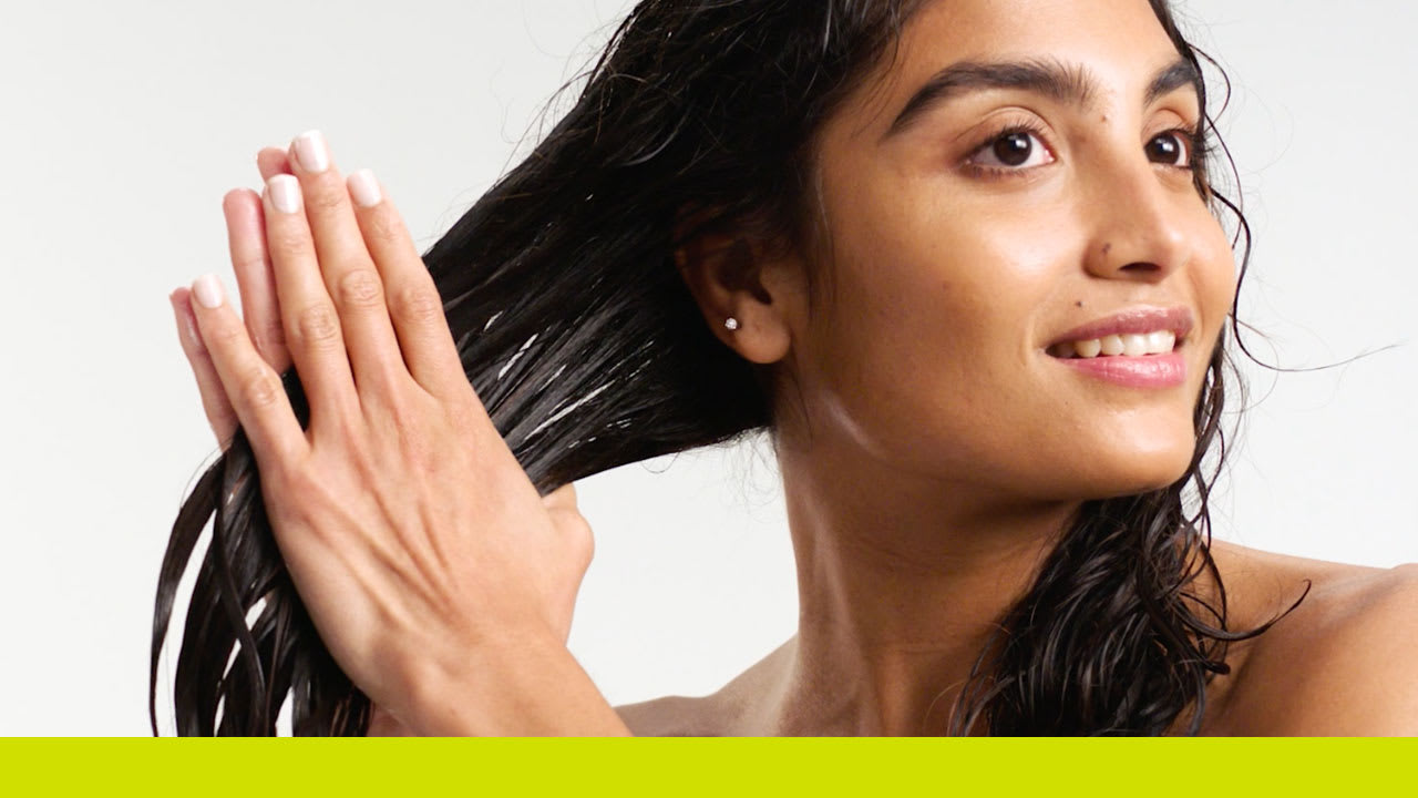woman applying styler to hair using prayer hands technique