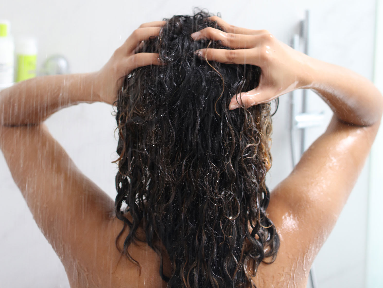 woman in shower washing dark curly hair