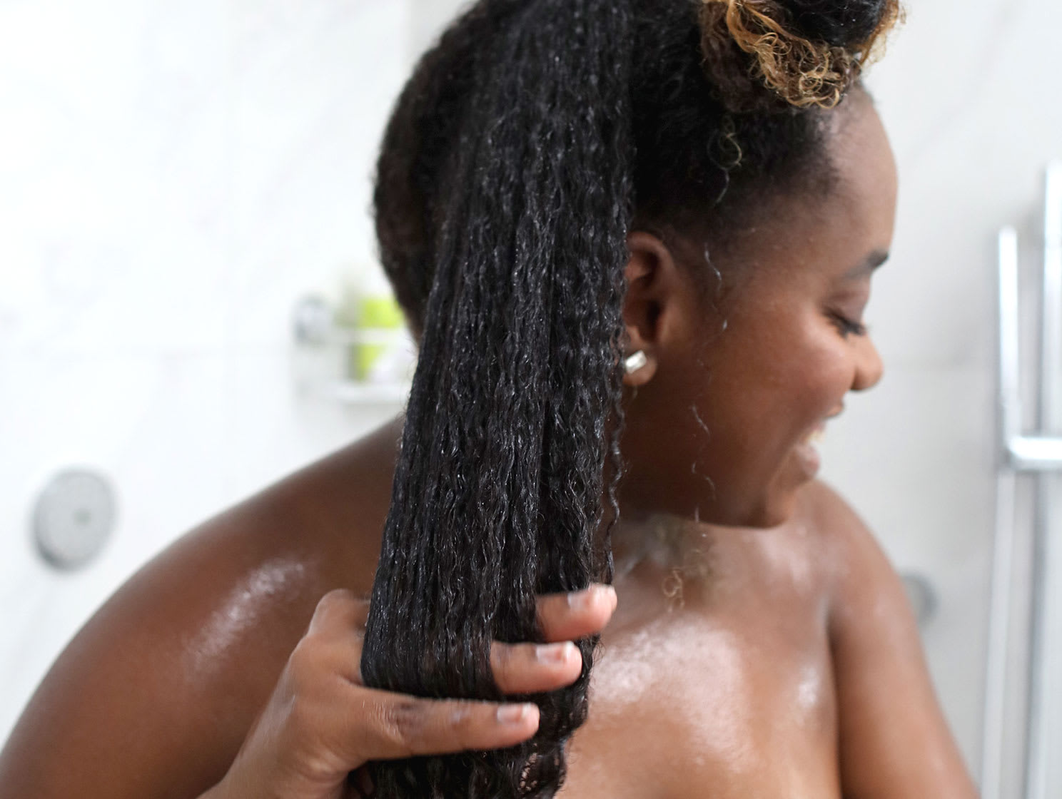 woman in the shower finger detangling super curly hair