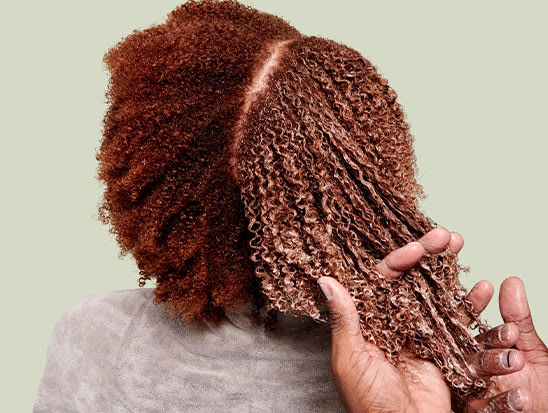 stylist running fingers through client's hair