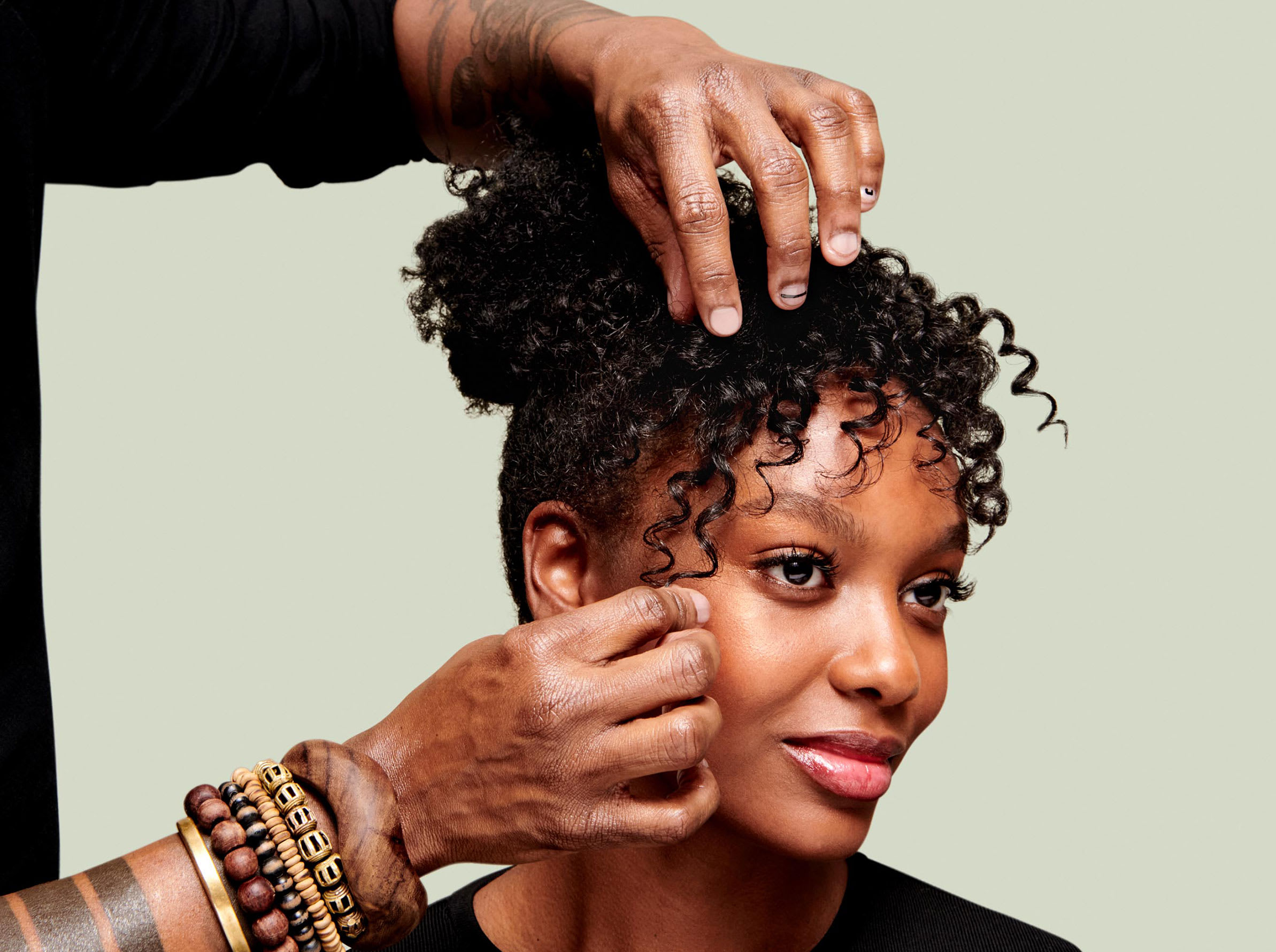 stylist touching curly hair of client
