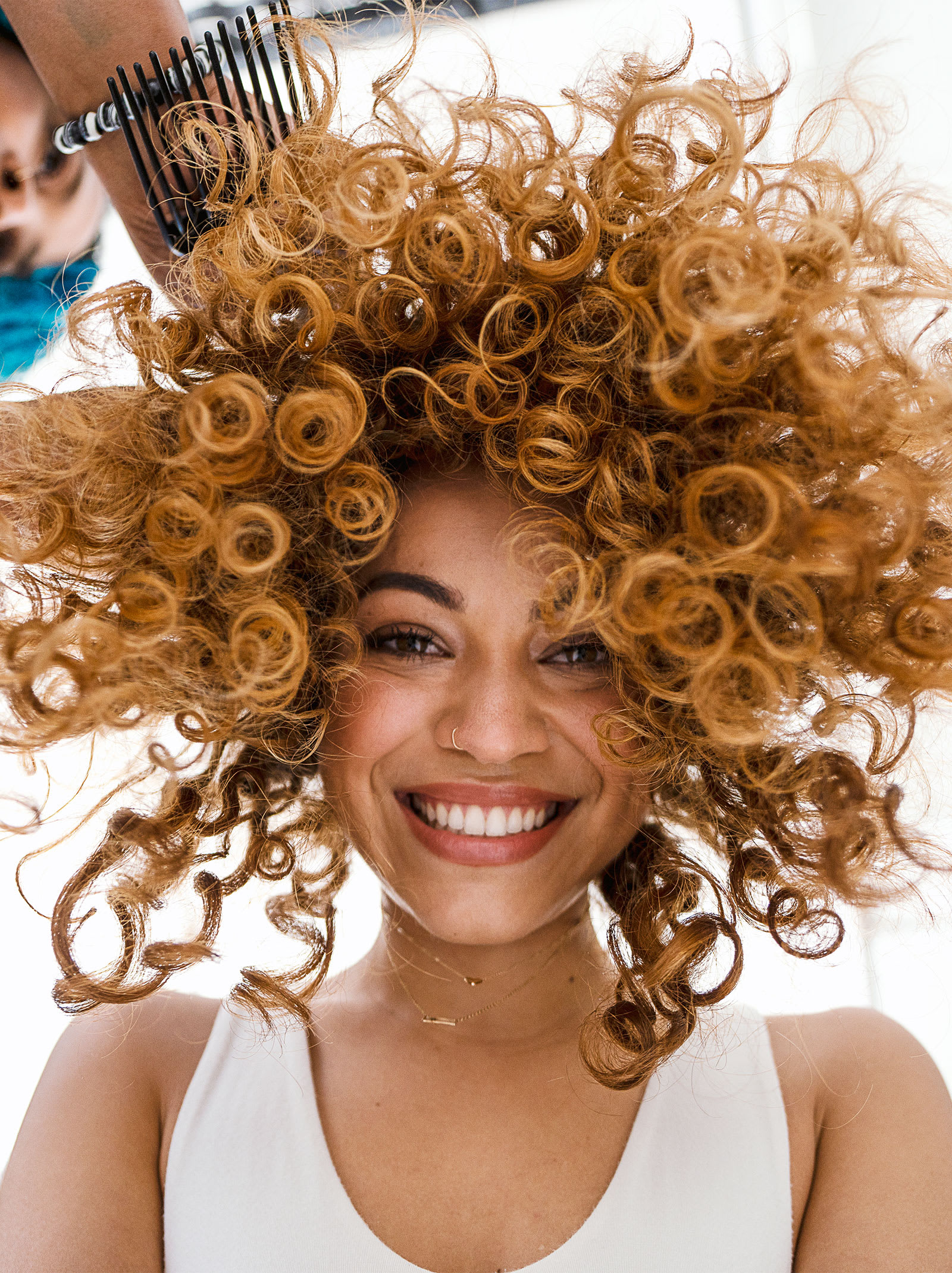 hair stylist with hands in woman's curly hair