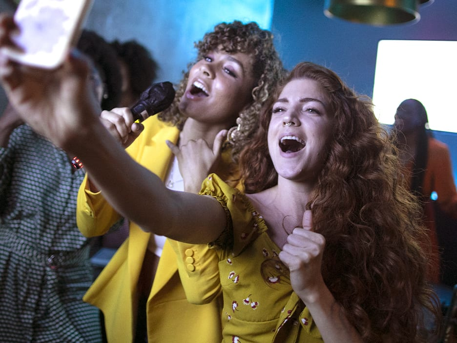 two curly girls singing and taking a selfie