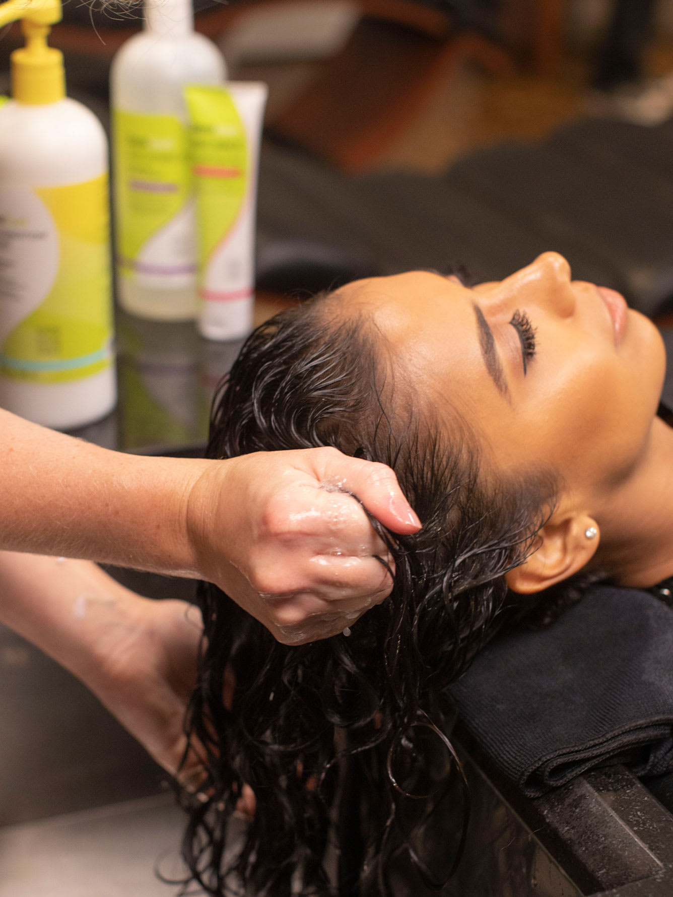 wavy client at the sink hands in hair