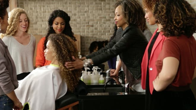 hair stylist washes woman's curly hair at a sink