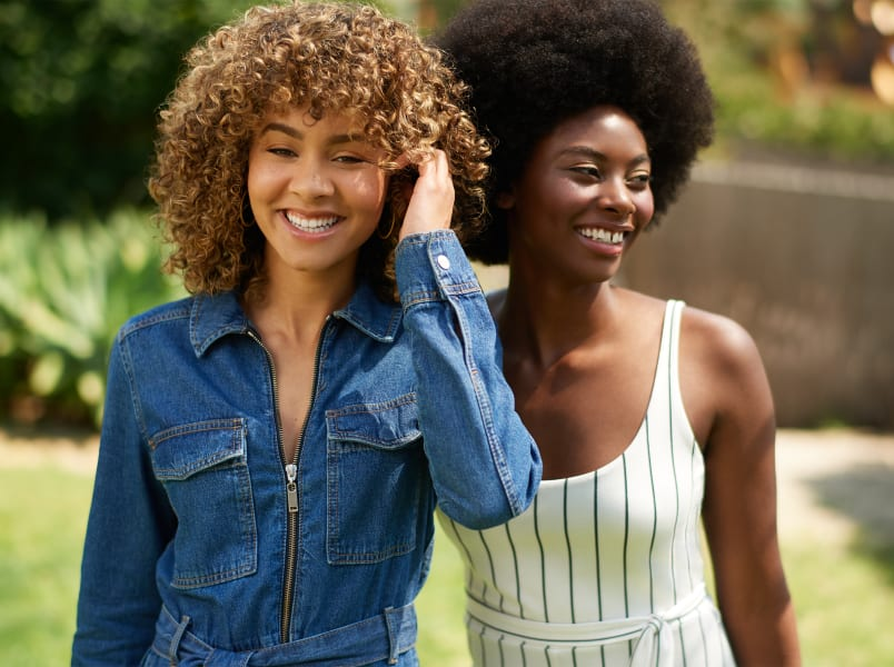 curly hair woman and super curly hair woman smiling