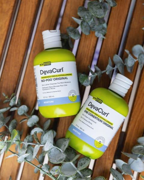 DevaCurl Fragrance Free Hypoallergenic Original Cleanser, Conditioner bottles with eucalyptus as decor