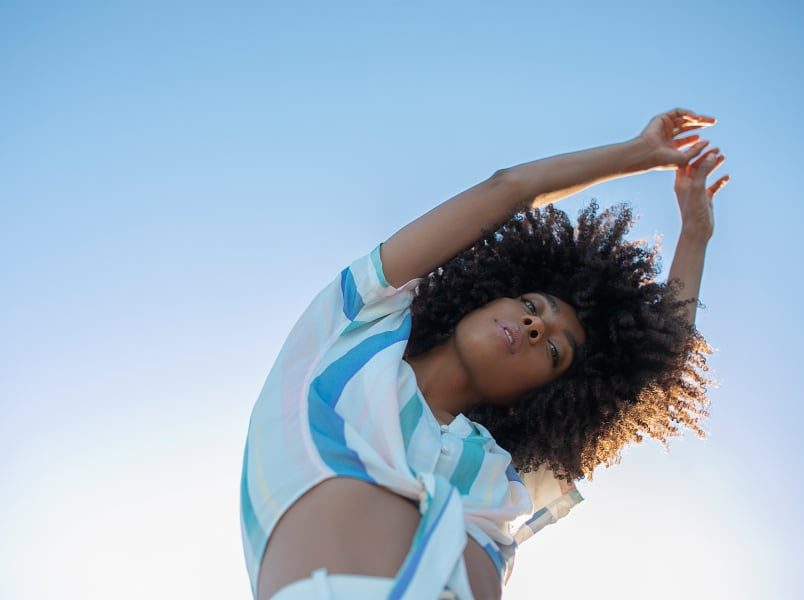 woman with super curly hair stretching her arms in the air