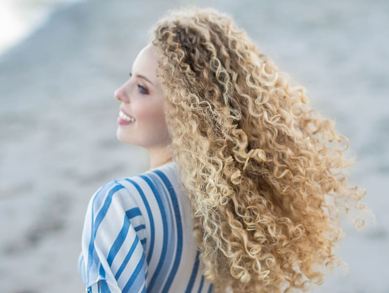 curly hair woman on a beach