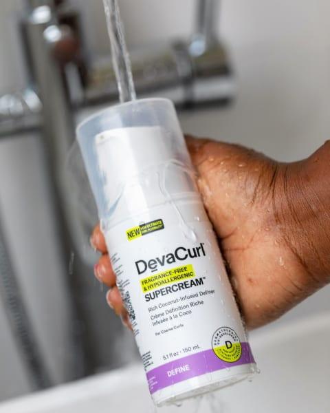 devacurl hypoallergenic curl cream bottle in hand