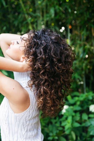 Woman with her hands in her long, dark curls