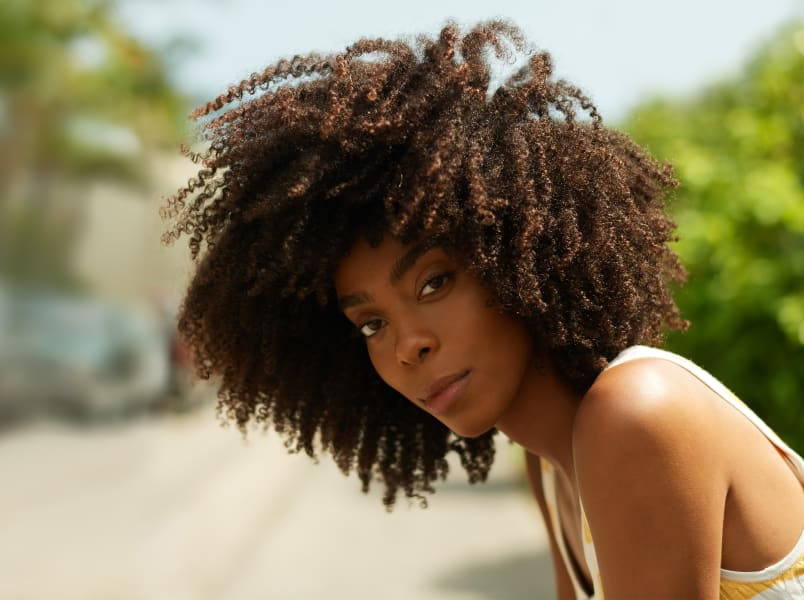 woman with dark super curly hair outside