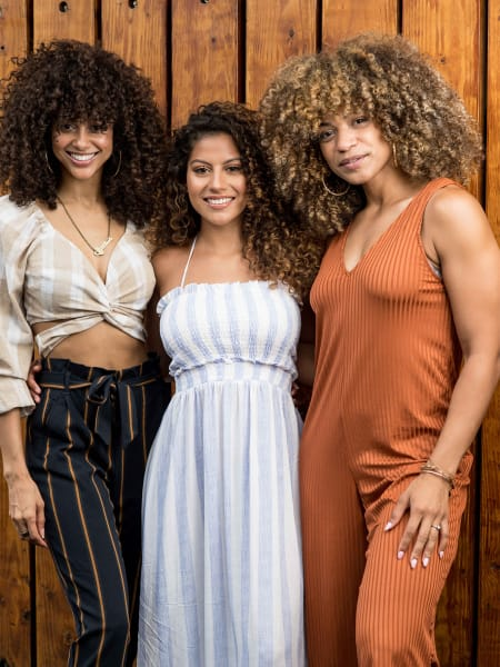 three curly hair women smiling