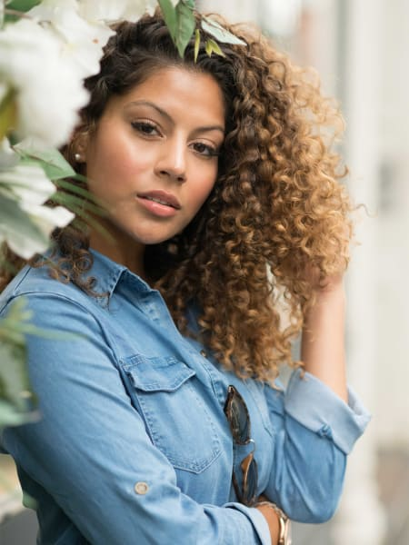 woman with curly hair in a denim shirt standing near white flowers