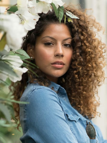 woman with light brown curly hair near flowers