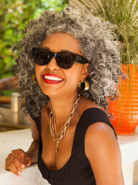 smiling woman with curly hair and sunglasses