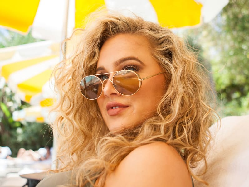 woman with wavy hair and sunglasses on face