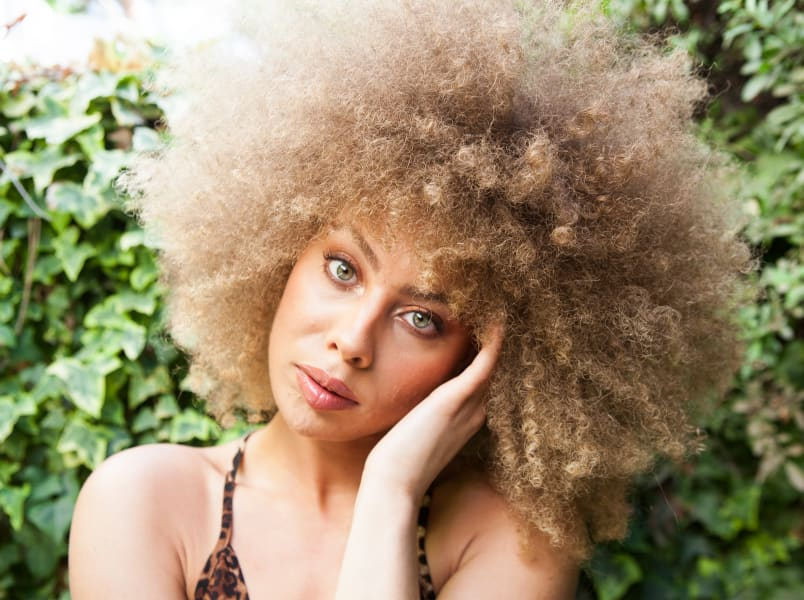 Blonde woman with super curly hair touching face