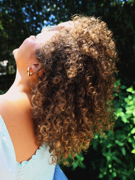 Woman with curly hair looking up