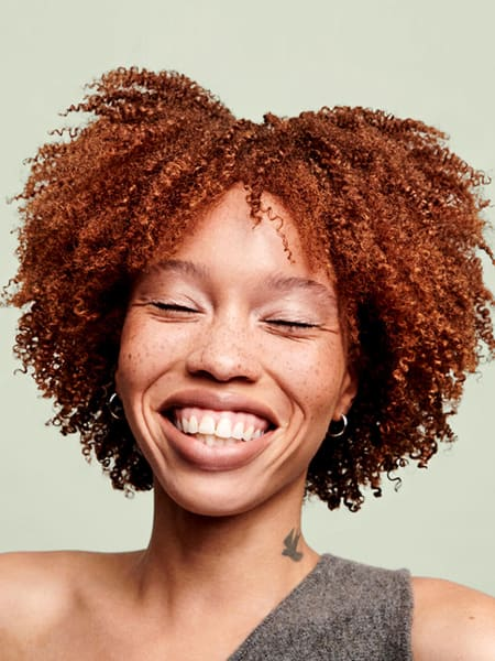 woman smiling with red coily hair