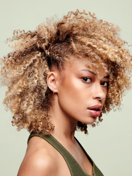 Woman with blonde curls, partially braided along her scalp