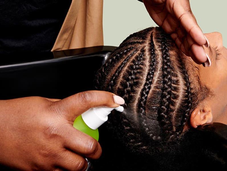stylist spraying Scalp Puri(pH)y™ on braids