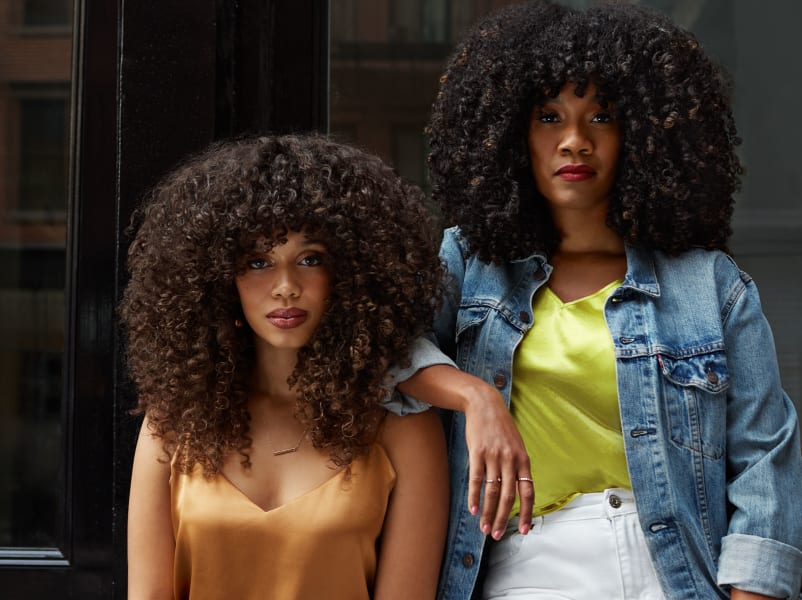 two women with voluminous super curly hair hanging out