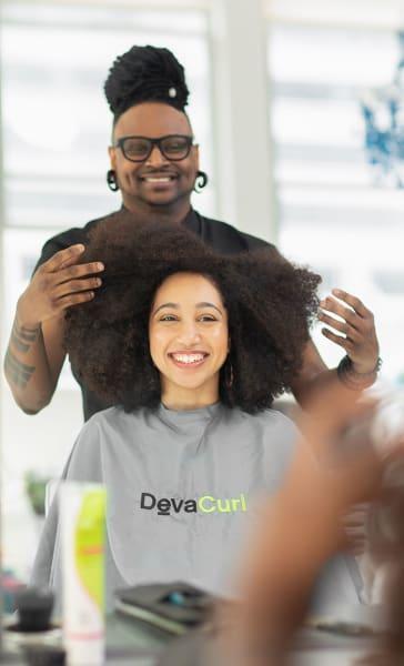 stylist fluffs curly hair woman's hair