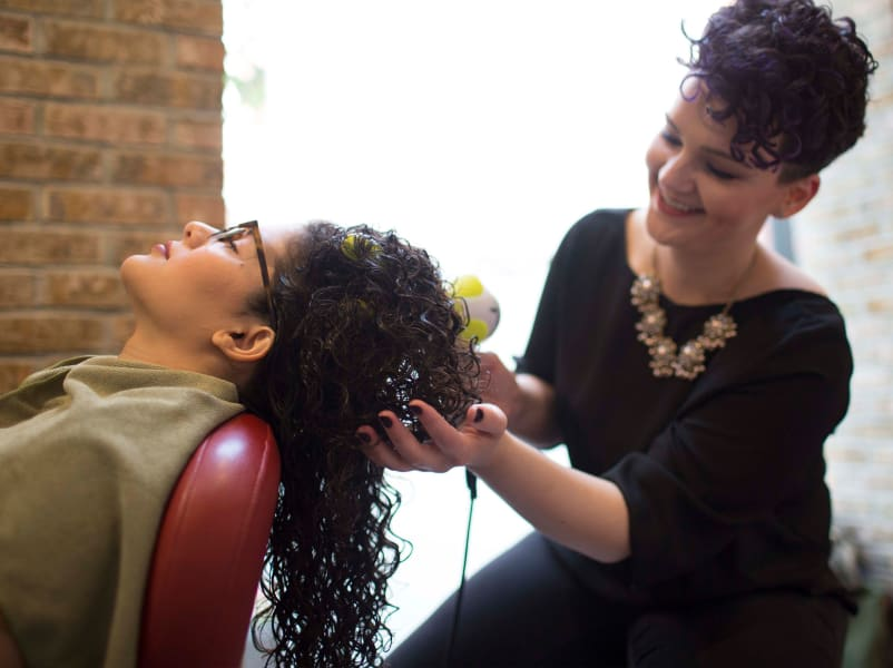 hair stylist blow drying curly hair with DevaFuser