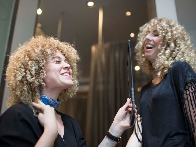 curly hair woman looks in the mirror smiling