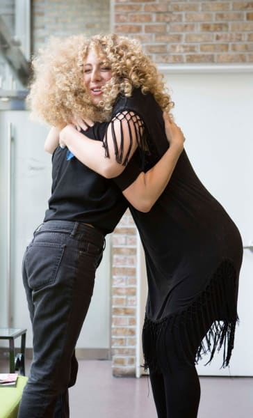 two curly hair women hugging